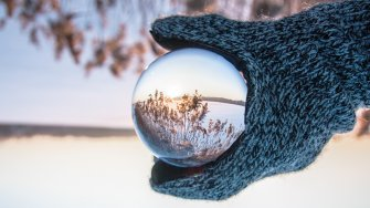 A hand holding a glass ball in a winter landscape