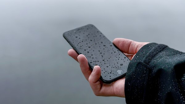 A hand holding a mobile phone in the rain
