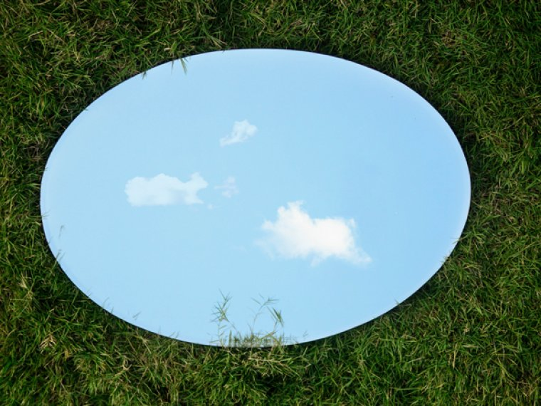 A round mirror on the grass